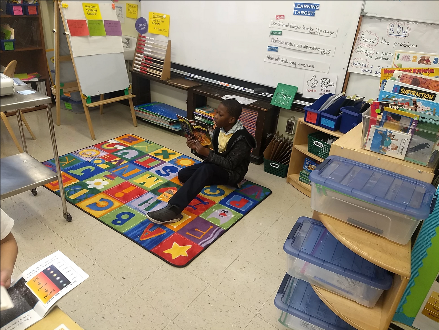 Student reading on the classroom rug