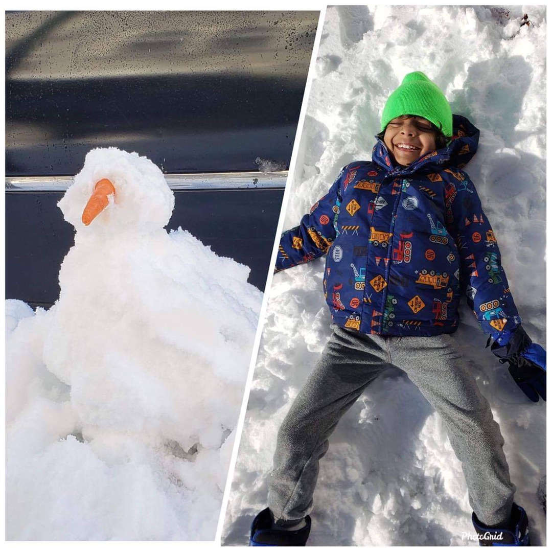 a small snowman with a orange nose and a kid lying on the ground