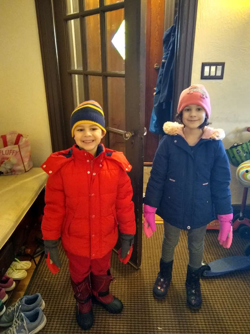 one kid in red coat and one in blue coat smiling ready to go outside