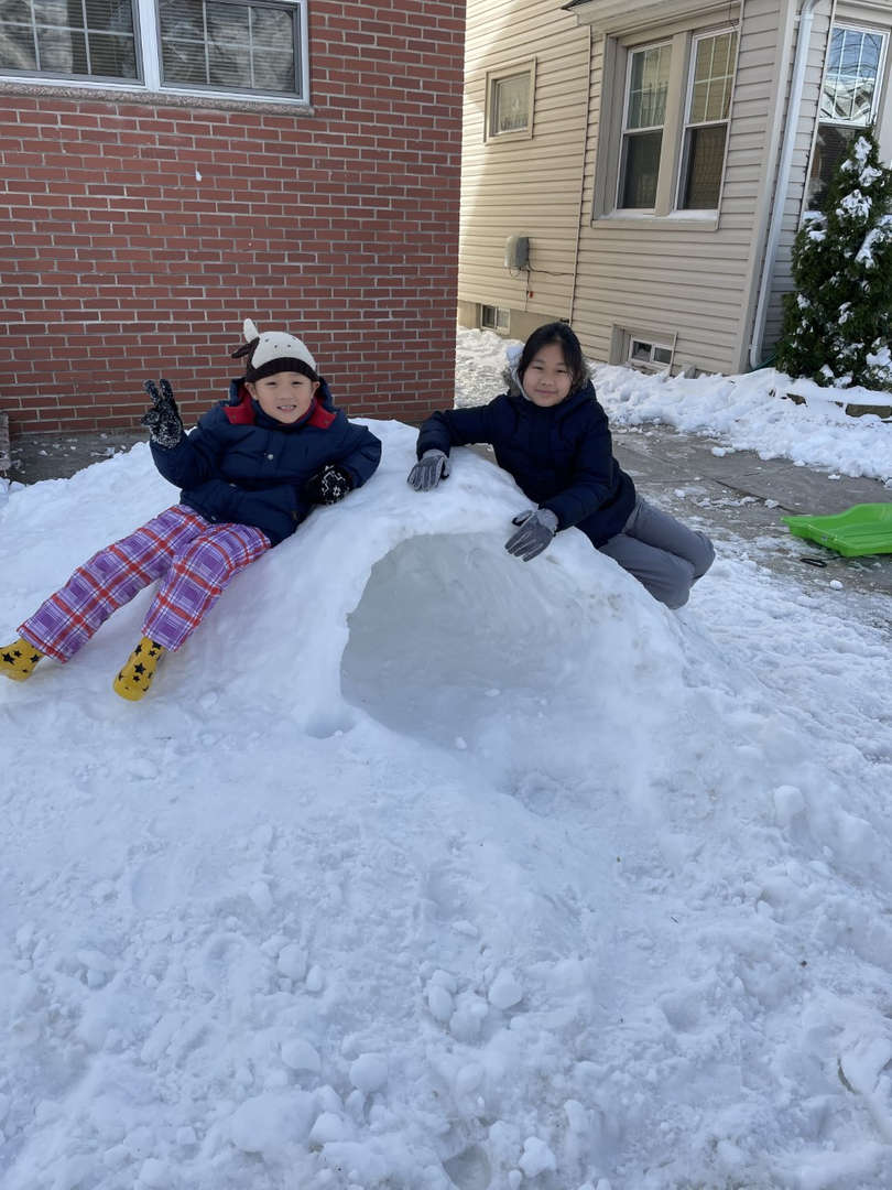 two kids sitting on the pile of snow
