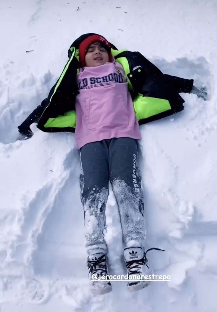 a kid in purple shirt lying down in the snow