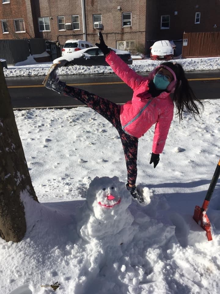 a girl making a fun gesture in the back of a snowman