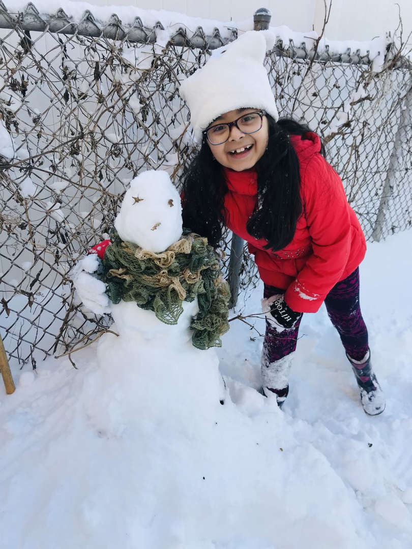 a girl in red coat with a snowman in the snow