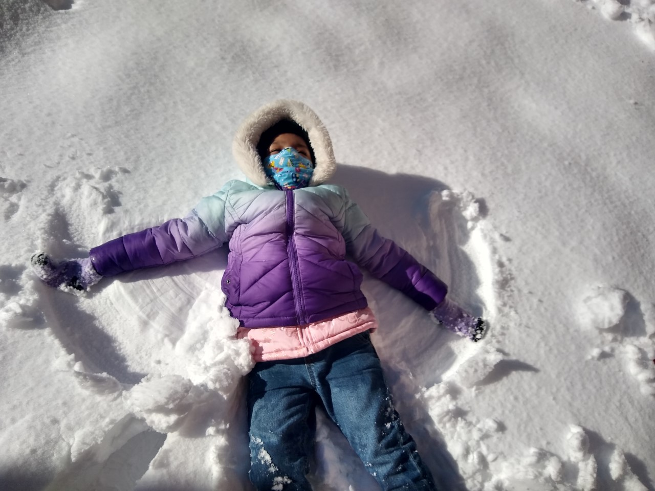 a girl making a snow angel on the ground