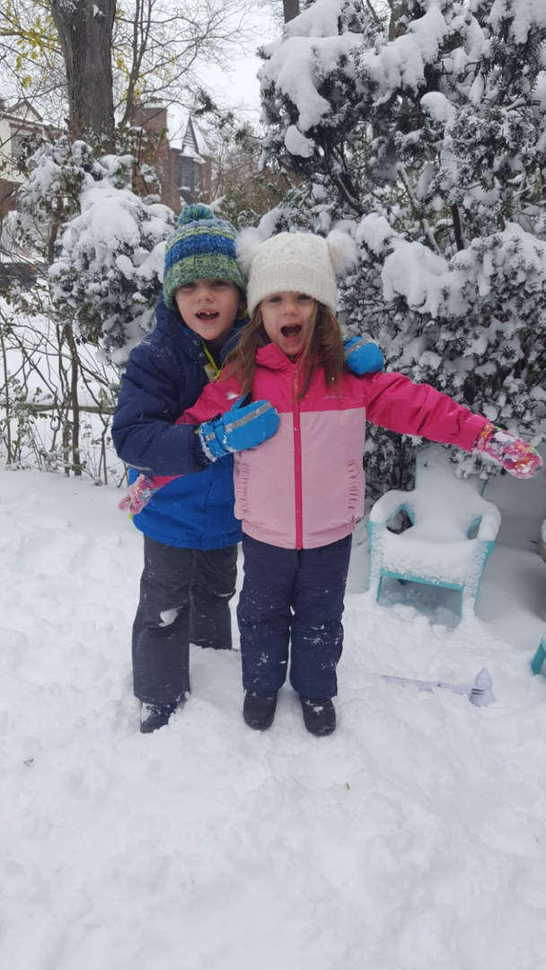 a boy in blue and a girl in pink smiling in the snow
