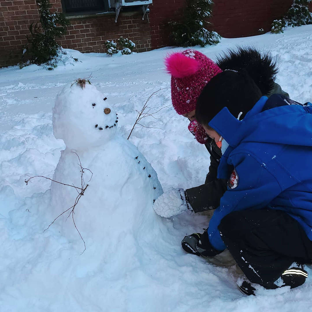 two children putting buttons on a snowman