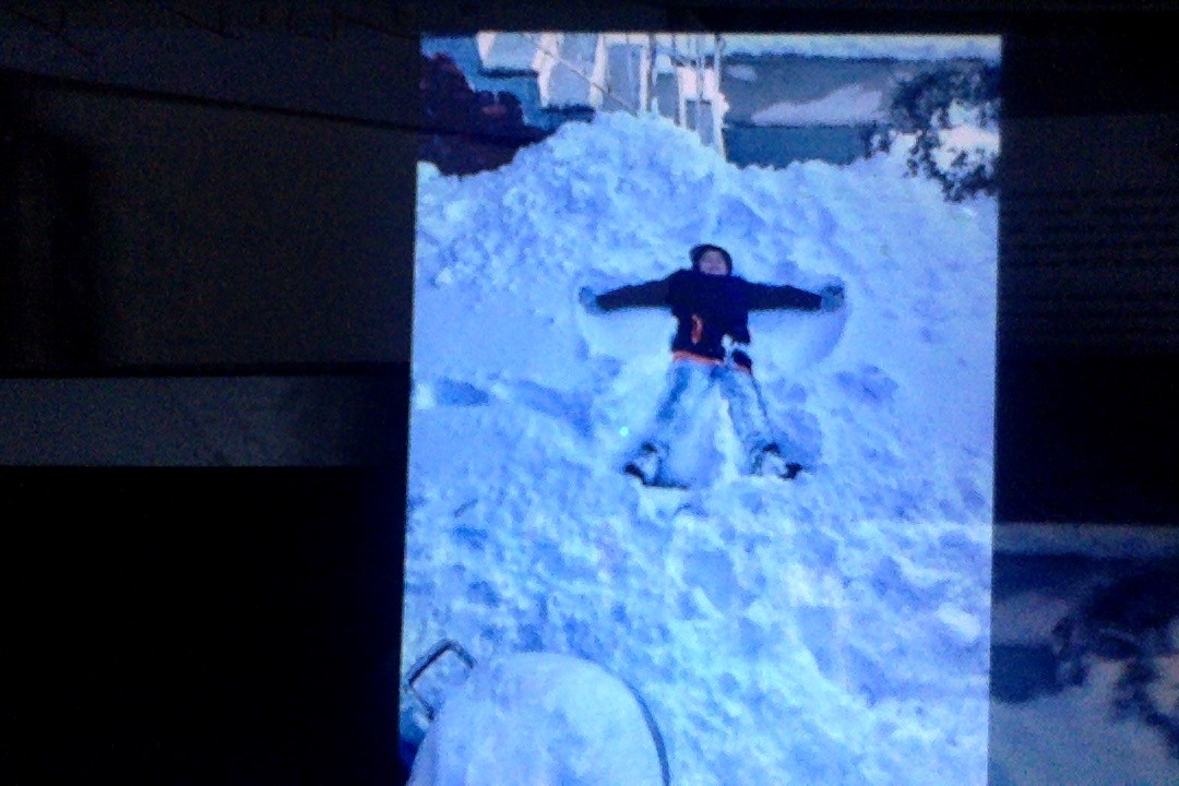 a boy making a snow angel on the ground