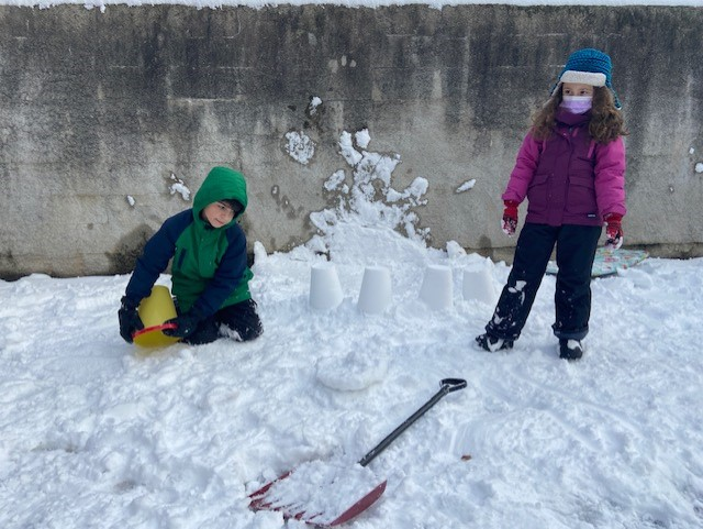 boy and girl playing in the snow building castle