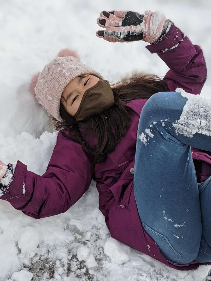 a girl on the ground with a mask on playing in the snow