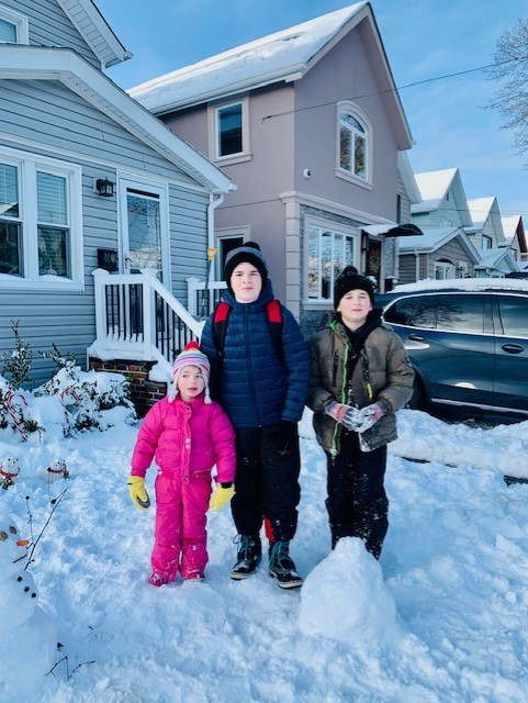 three kids standing in front of the house in the snow