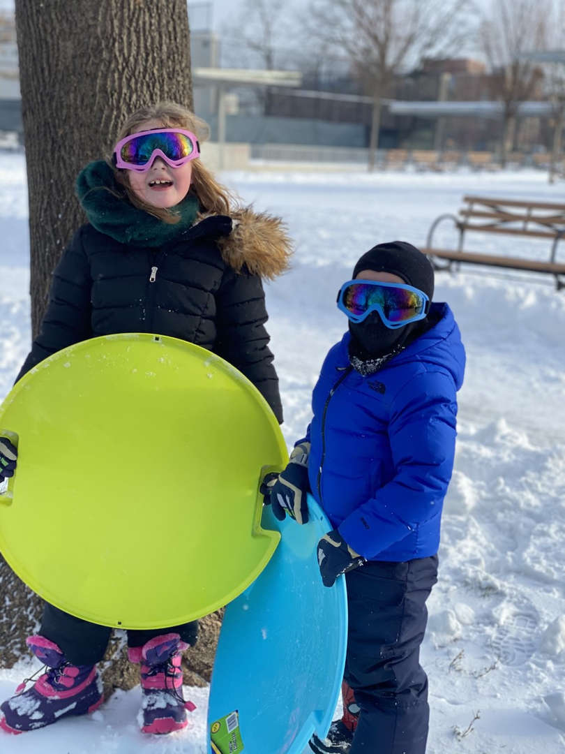 two kids holding a yellow sled