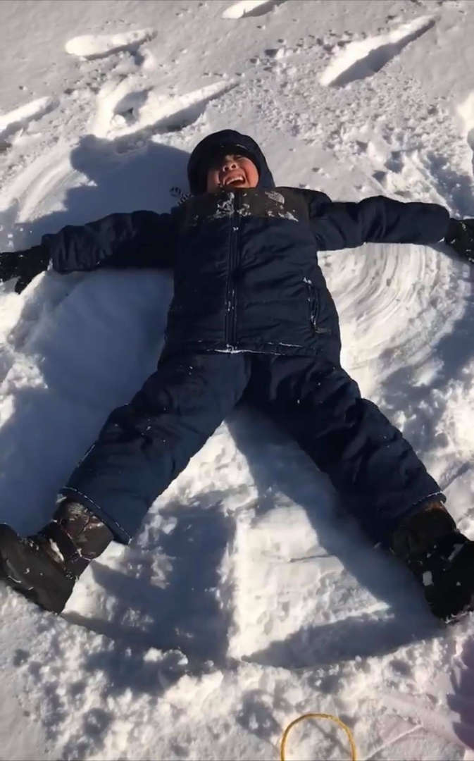 a boy making a snow angel