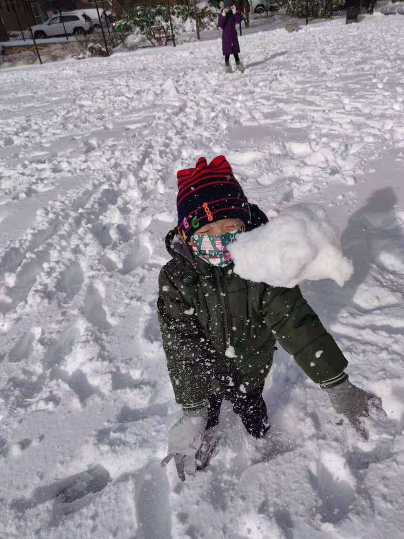 a kid with a mask on with snow falling