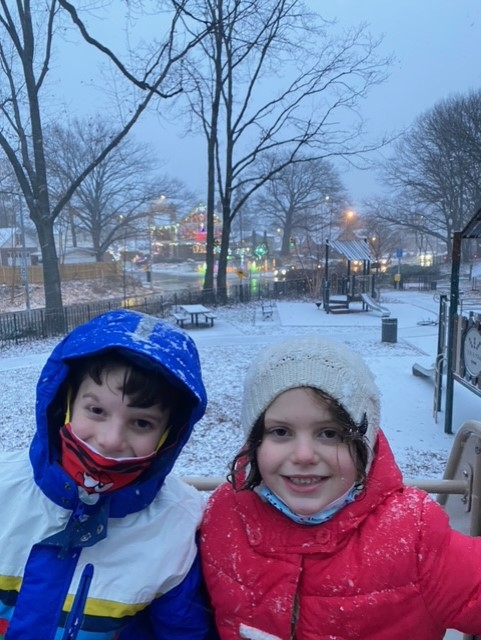 one boy and one girl smiling while its snowing outside