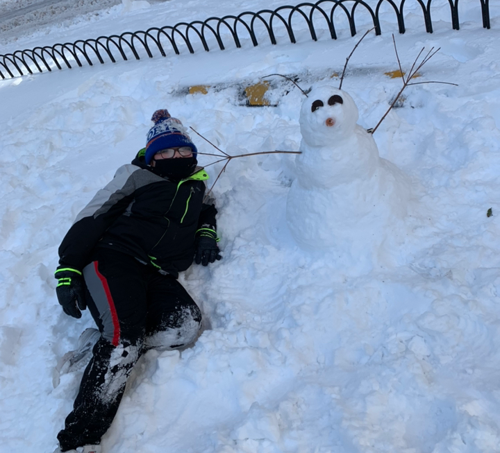 a kid with a snowman with sticks