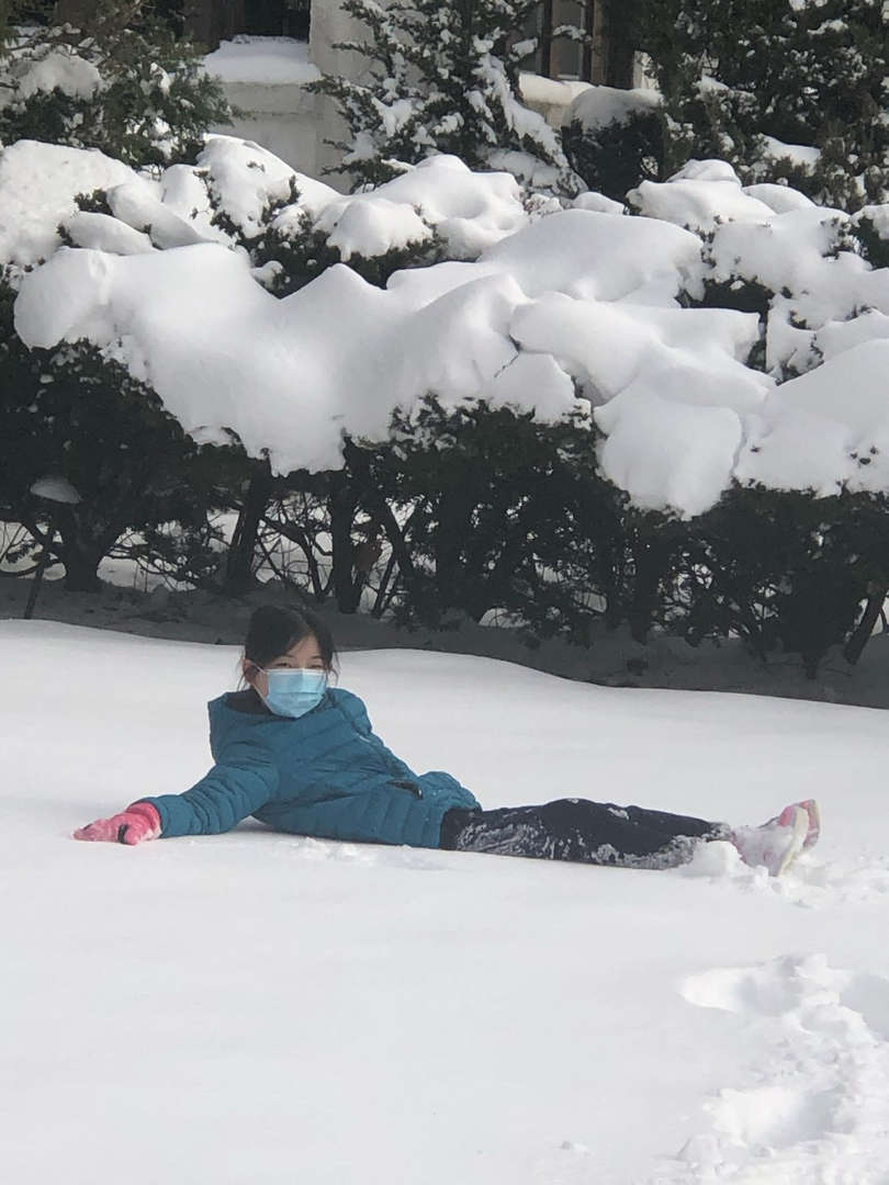 a girl in green on the ground in the snow