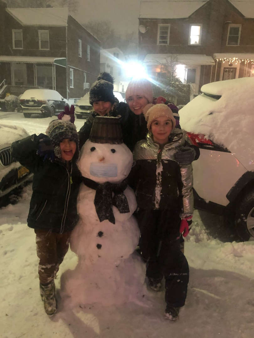 two kids and two adults in with a big snowman with a mask, hat and scarf