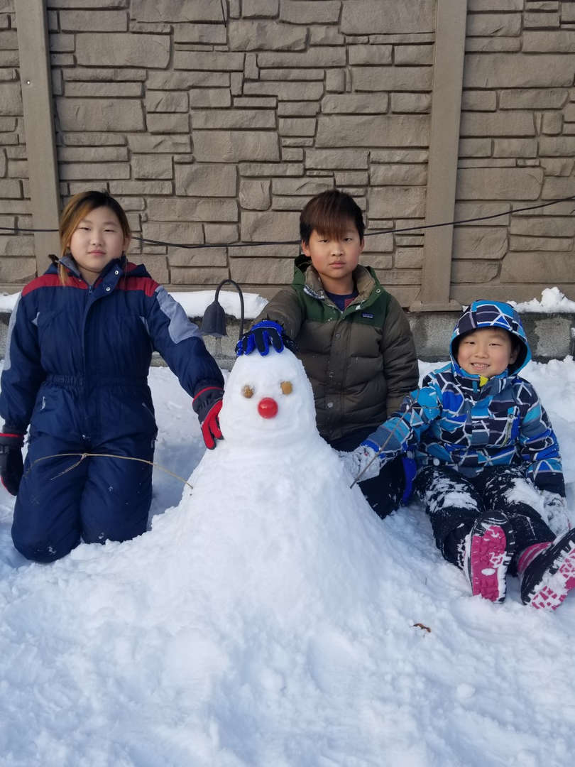 three kids with a snowman having fun