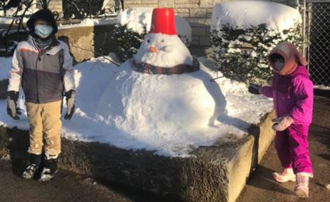a snowman with a red hat with two kids playing