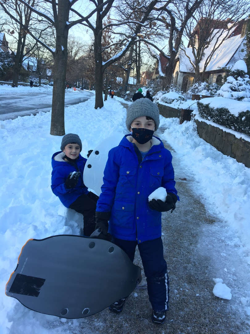two boys taking a picture in the snow one holding snow ball