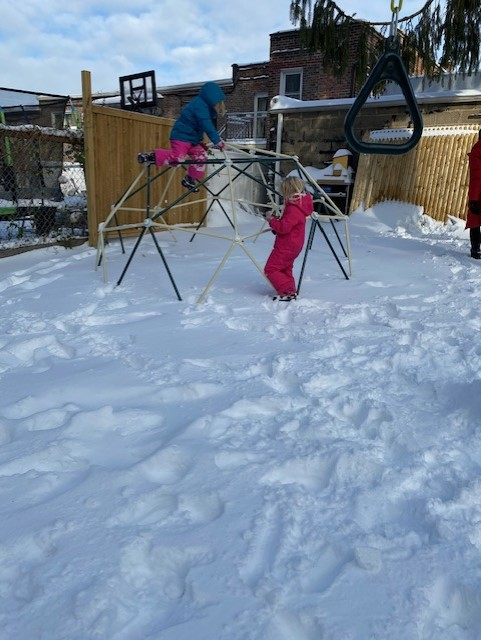 a girl playing in the snow in the playground
