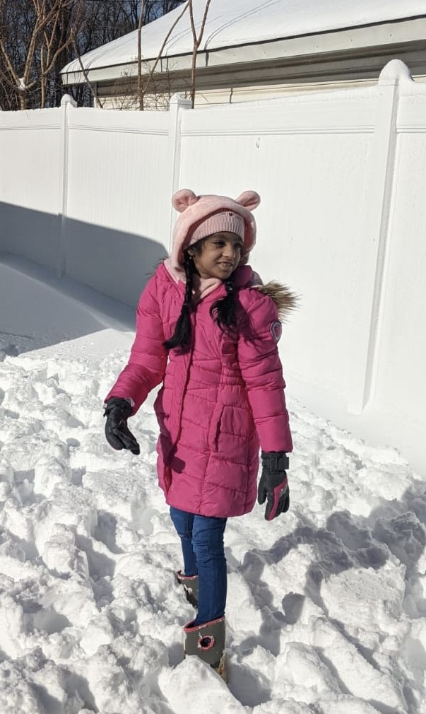 a girl in pink coat and pink hat smiling in the snow