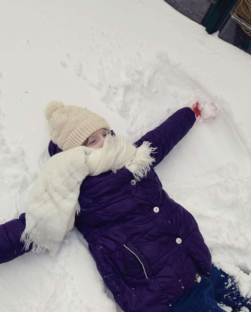 a girl in white hat and scarf lying on the ground in the snow