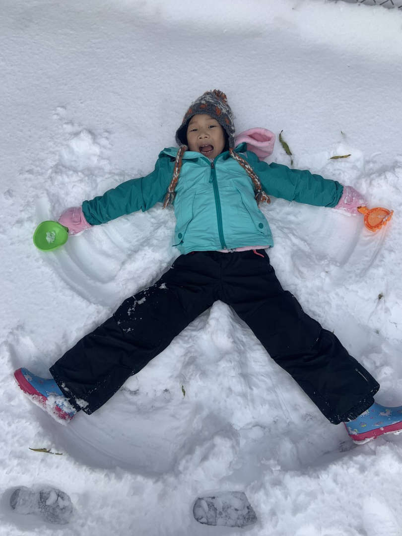a girl on the ground making a snow angel