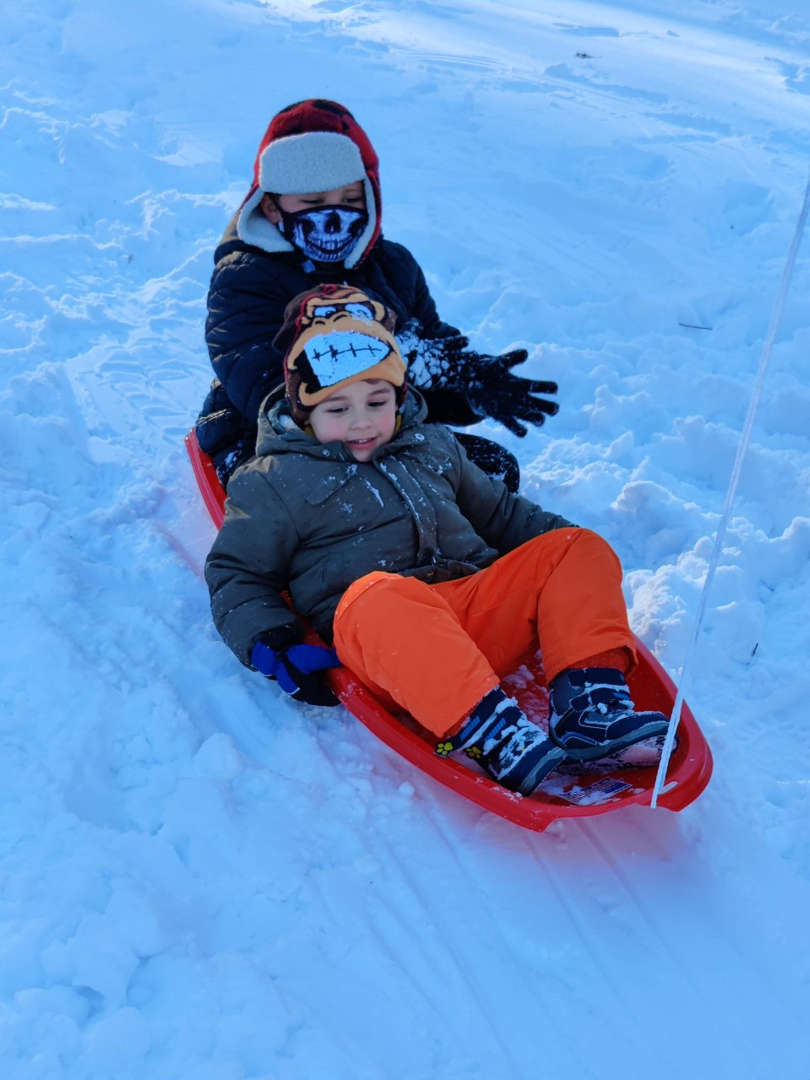 two kids on a sled smiling