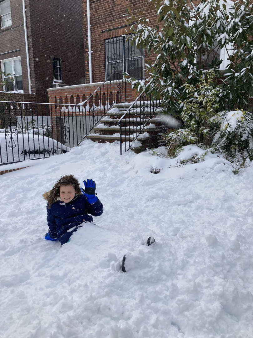a kid lying down on the snow in front of a house