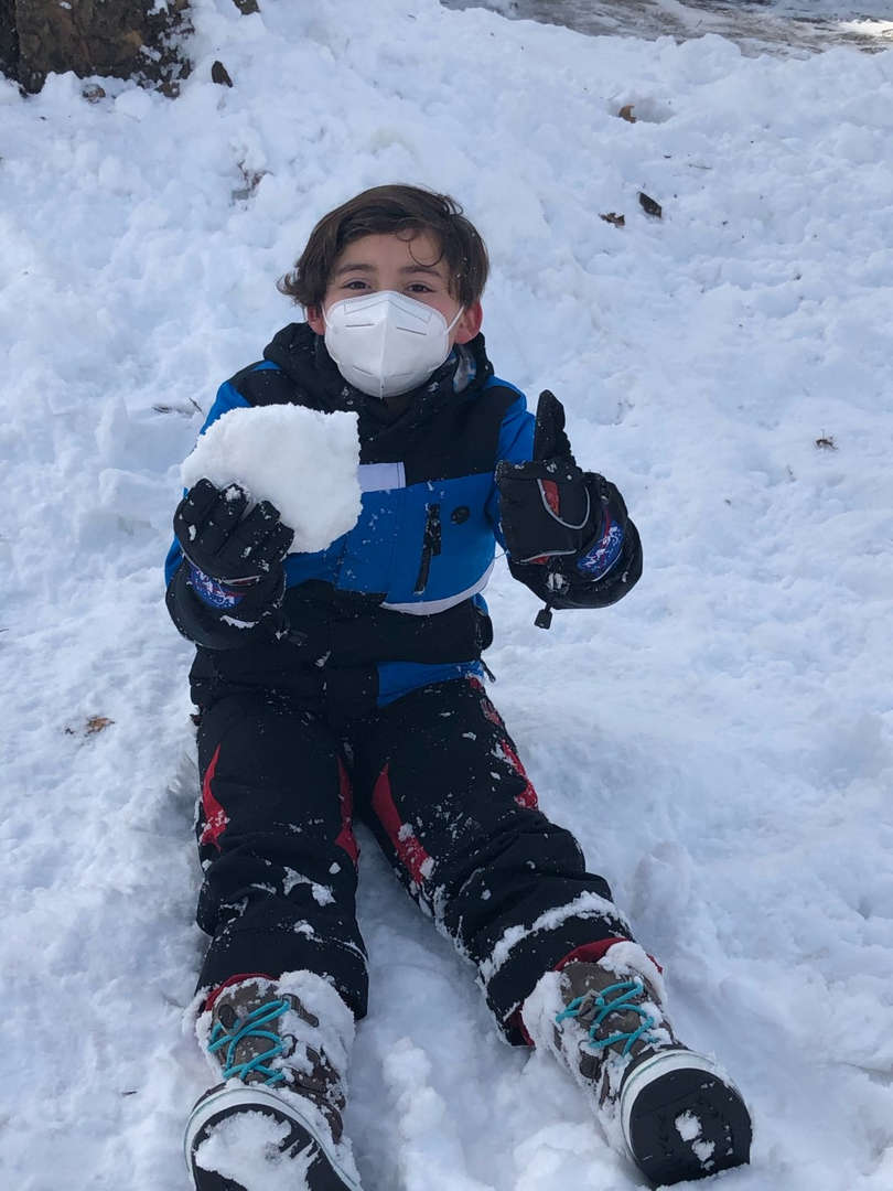 a boy with snow and thumbs up sign
