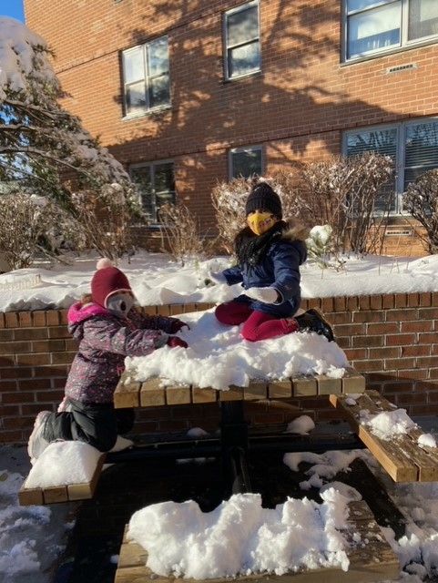 two kids sitting on a pile of snow
