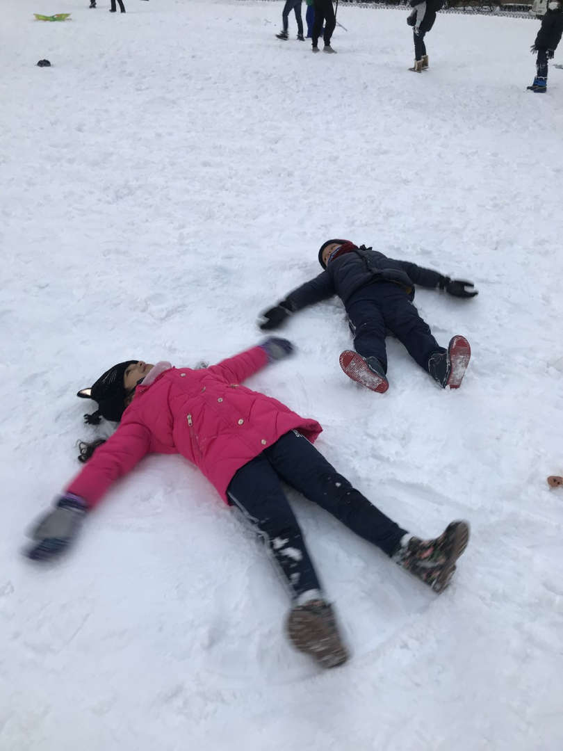 one girl in pink and a boy lying on the ground