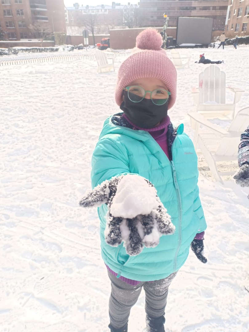 a girl in blue jacket holding a snow