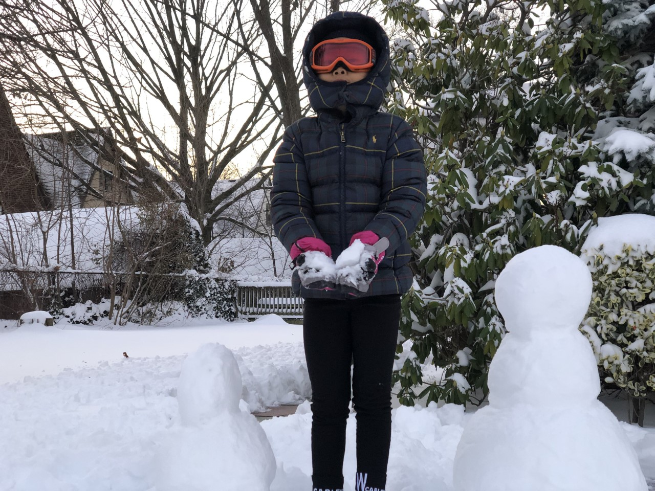a boy in black standing next to a snowman