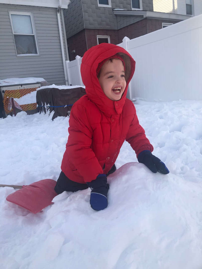 a kid in red coat smiling in the snow