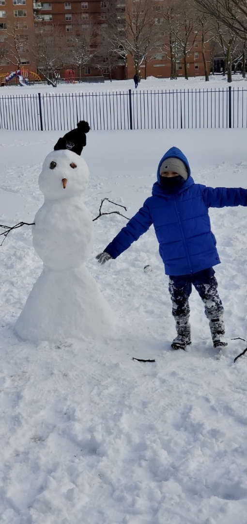 a boy in blue coat next to a tall snowman