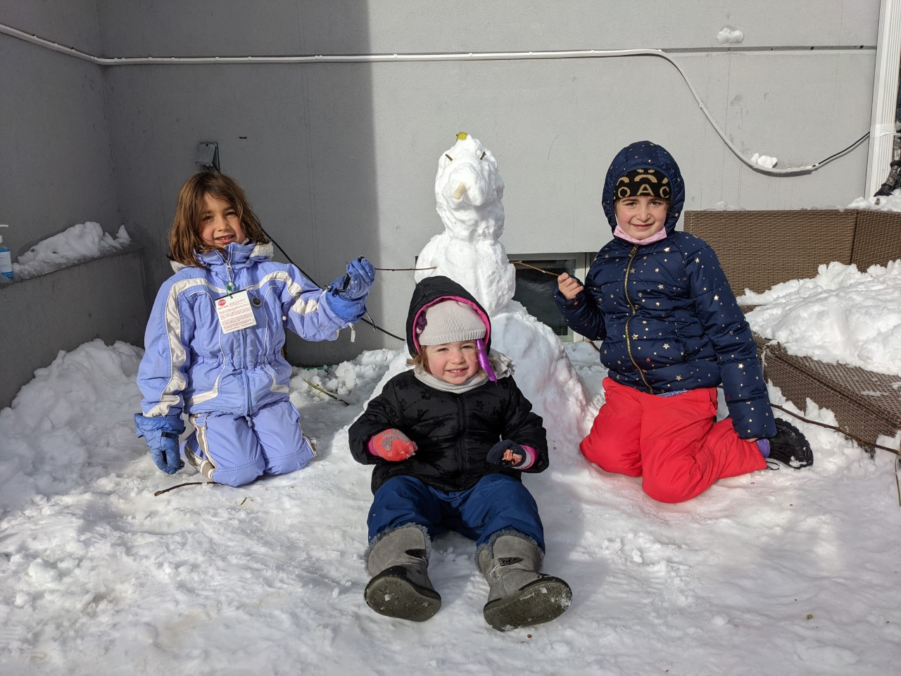 3 children on the ground with a snowman
