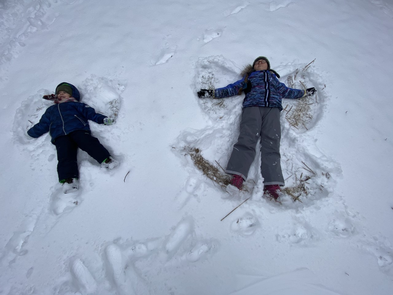 two kids making a snow angel on the ground