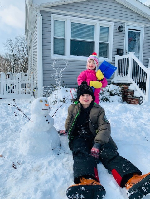 a boy in a brown jacket and a girl in pink with a snowman