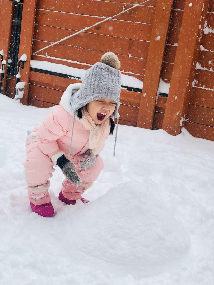 a girl in pink snow suit smiling in the snow