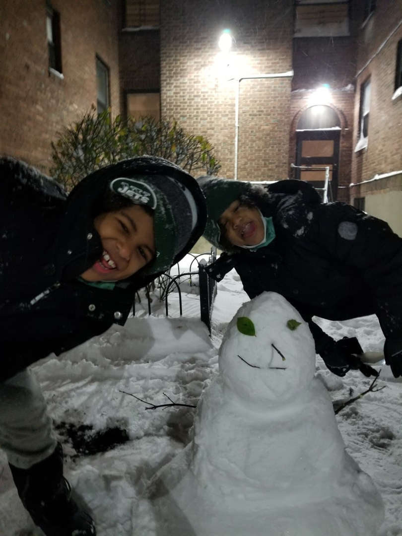 two kids taking a picture with a snowman