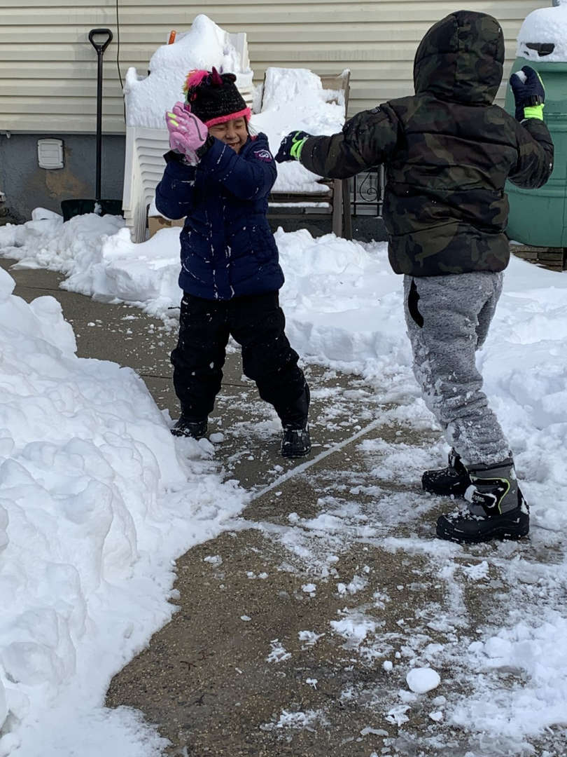 two kids standing on the side walk in the snow