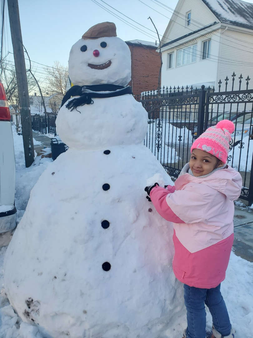 a girl in pink with a big snowman