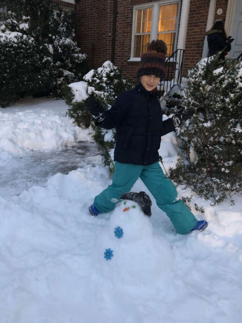 a kid in green pants behind a snowman