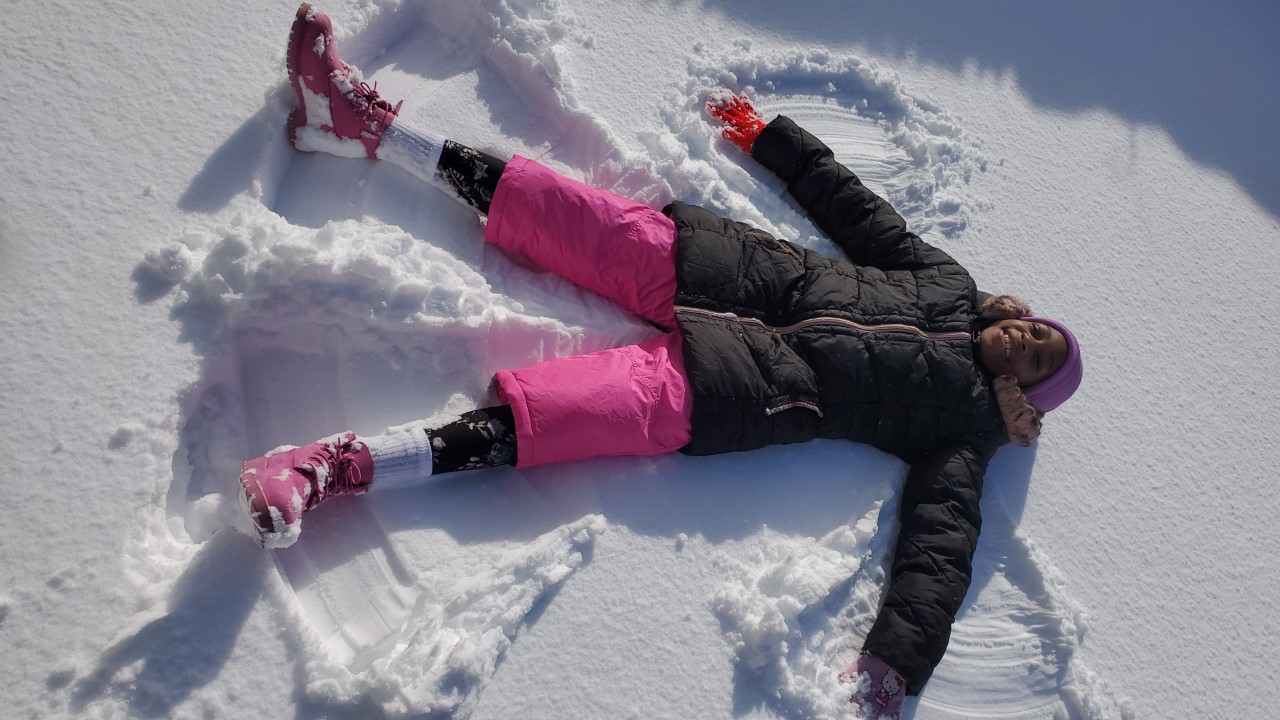A girl lying on the ground making a snow angel