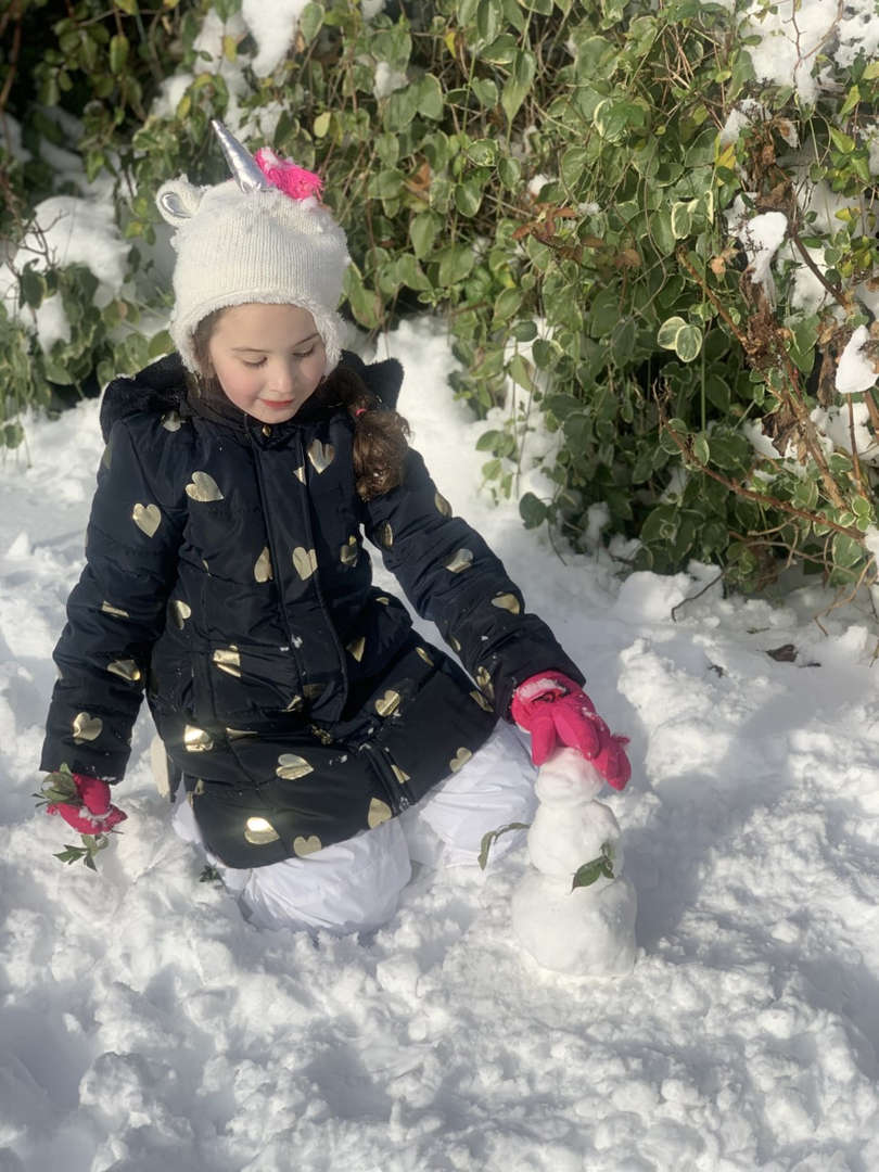 a girl in pink gloves making a small snowman
