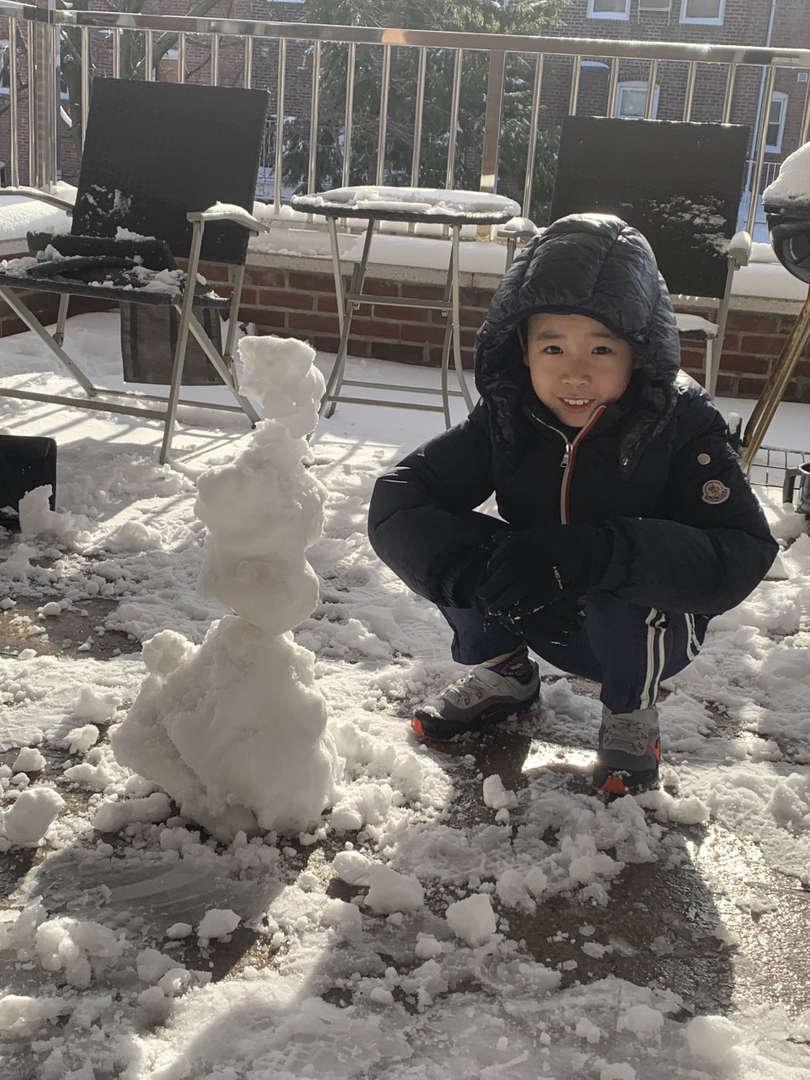 a boy in black coat with a snowman smiling