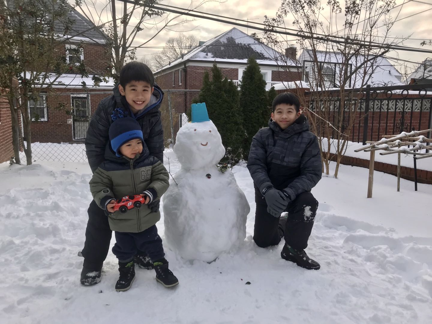 Three kids standing next to a snowman with a blue hat