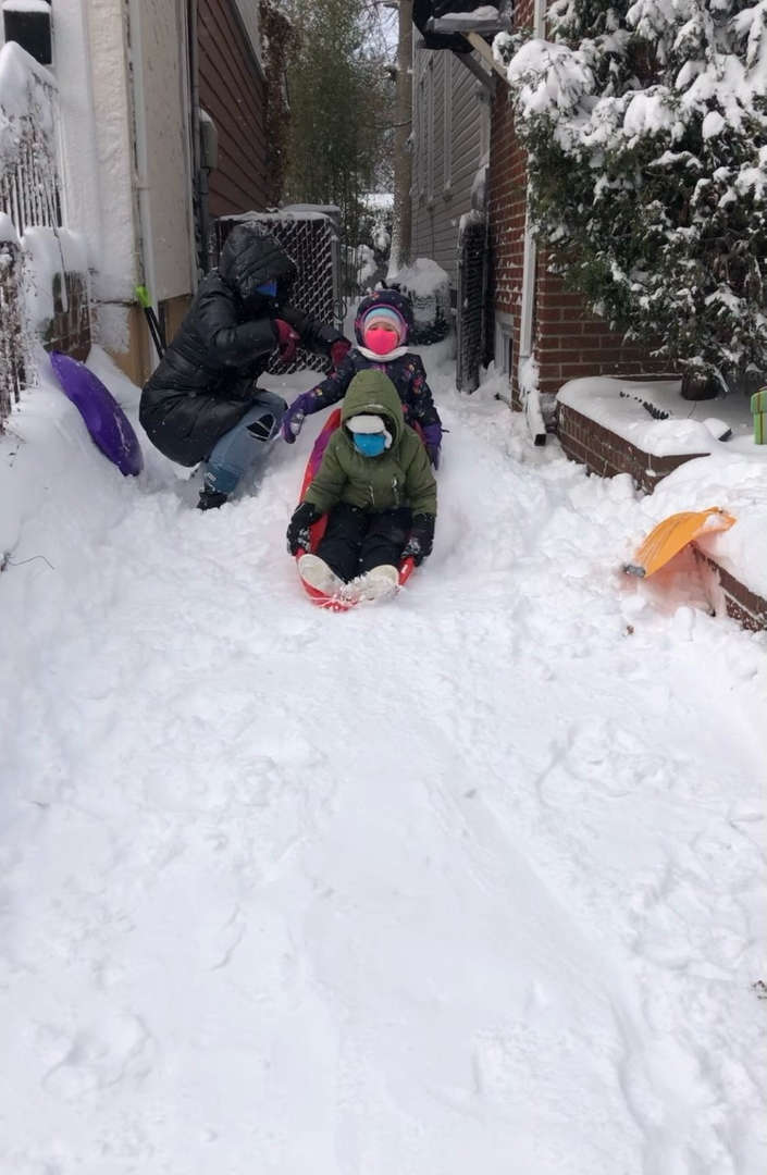 two kids riding a sled